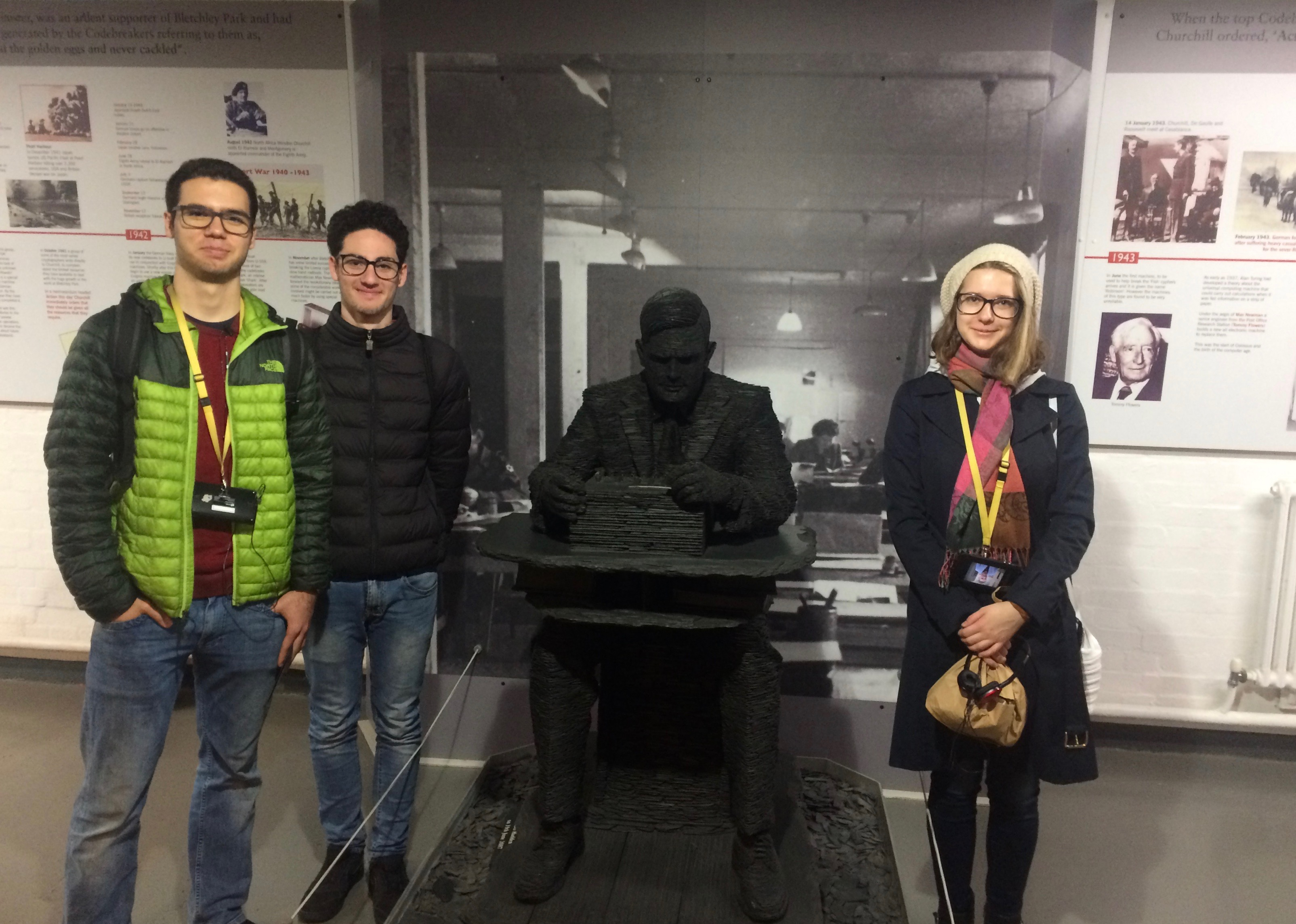 three students posing with statue